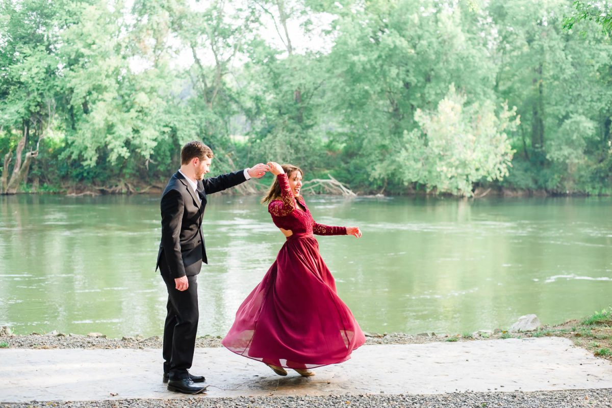 guy in a black suit twirling a girl in long dress outside