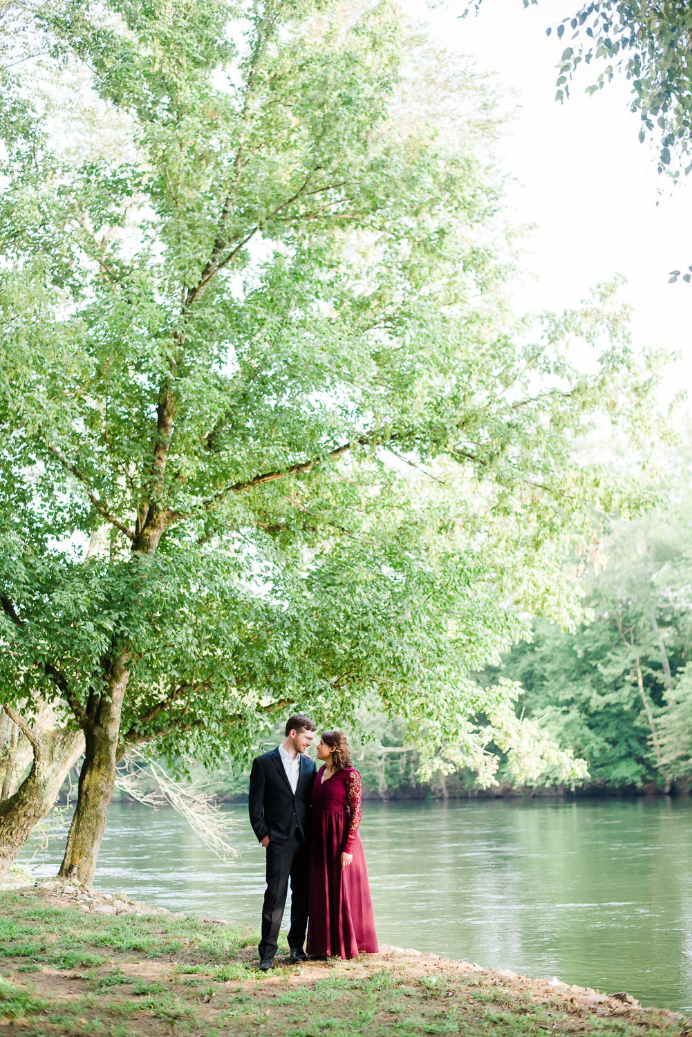 two people outside under a tall tree by the hiwassee river in the summer