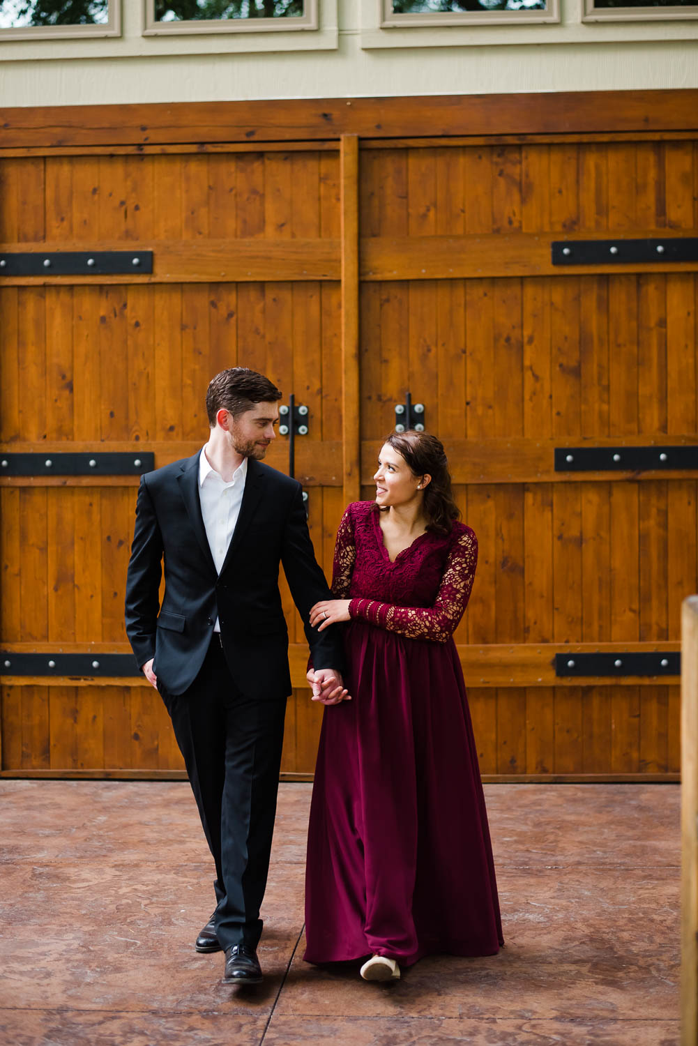 two people outside walking in front of the huge wooden doors at Hiwassee river weddings venue