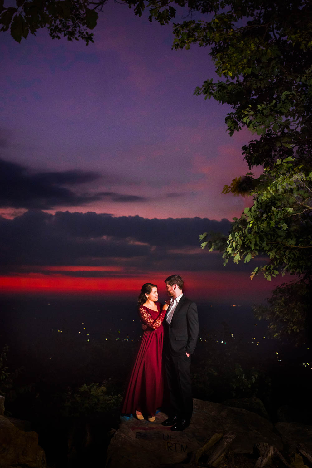 two people outside at night wearing a red dress and black suit