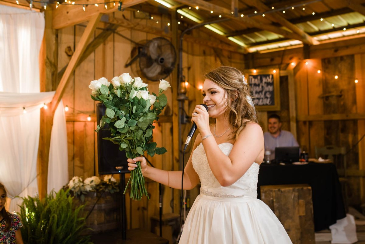 bride with two dozen long stemmed white roses