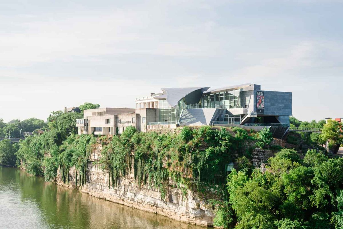 Hunter museum of art with lots of vines growing up the rock clif. viewed from the river