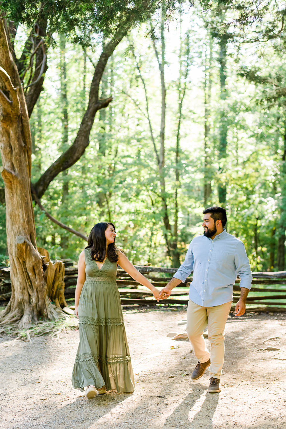 two people outside holding hands laughing as they walk