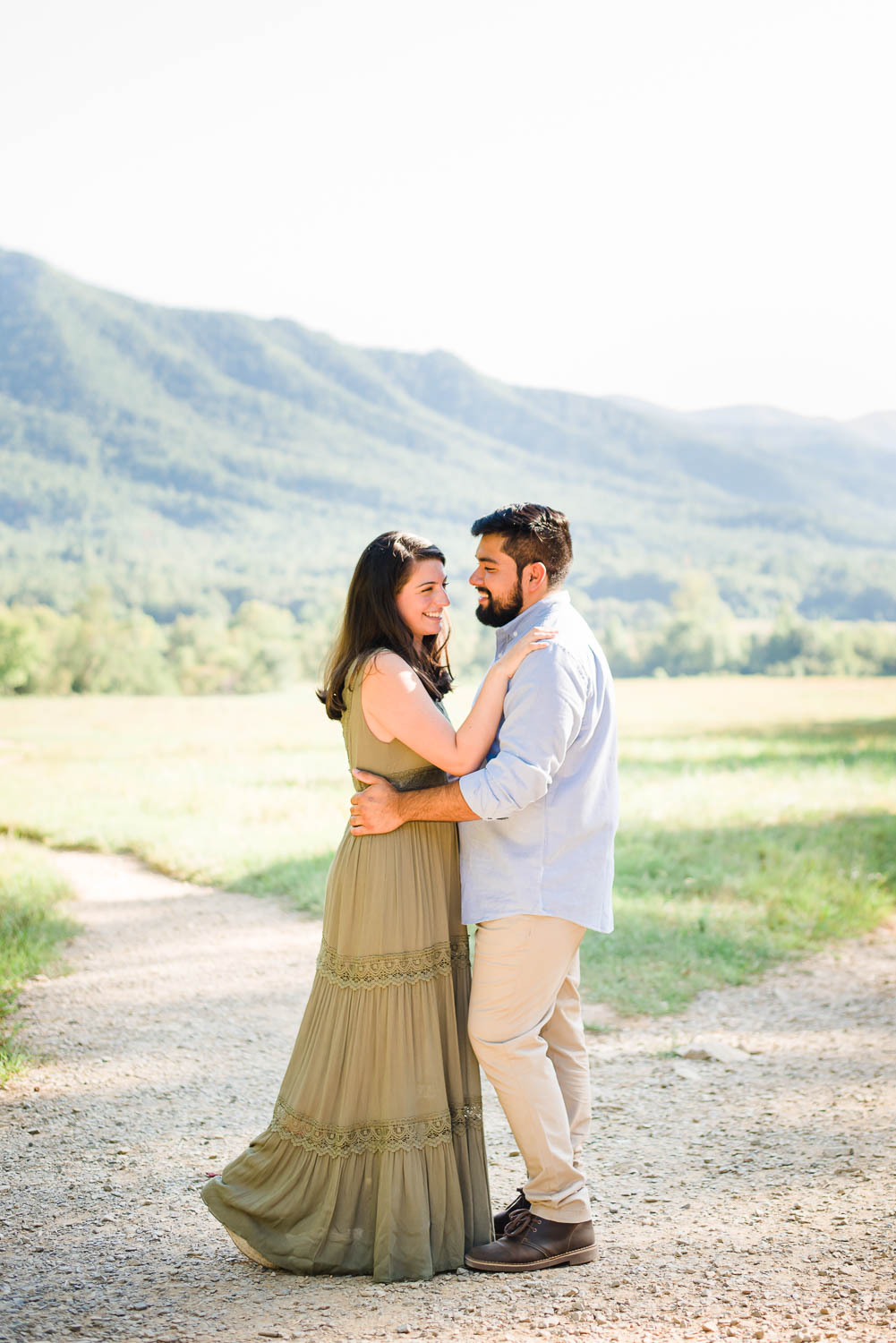 two people dressed for engagement photos in front of mountains