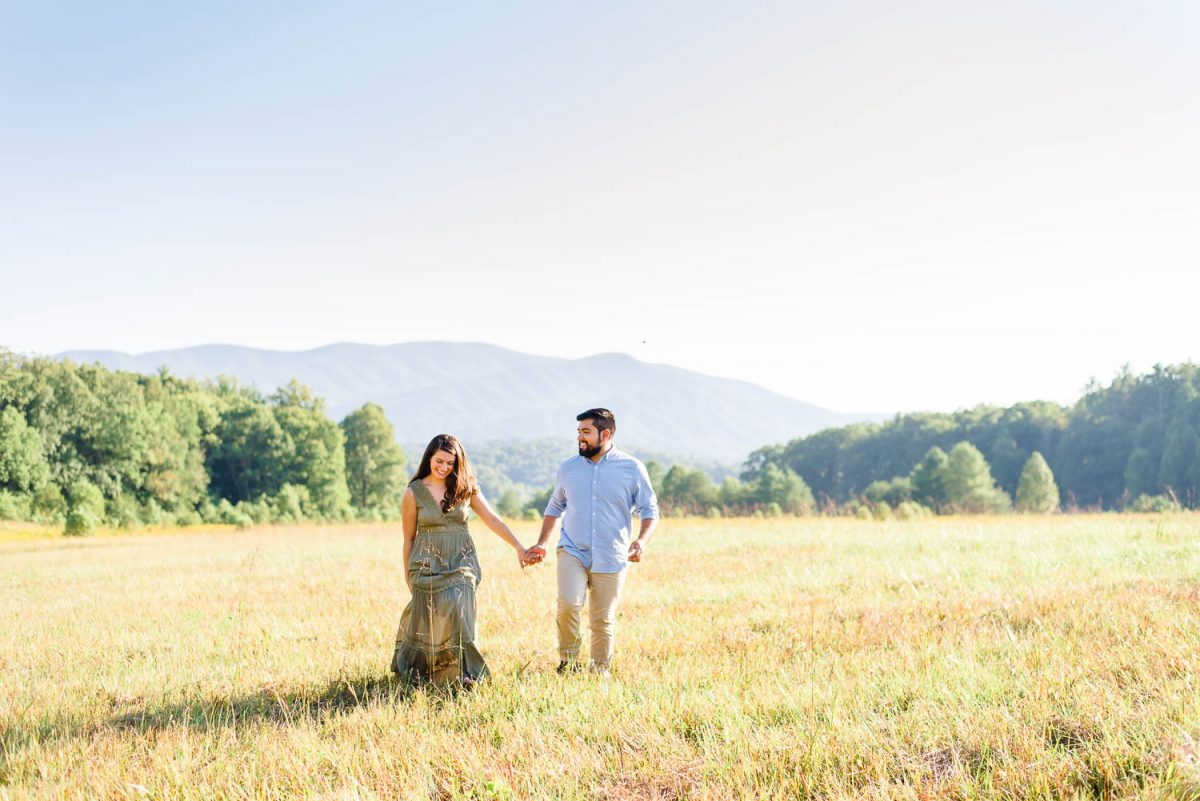 engaged couple walking through a field in Townsend TN