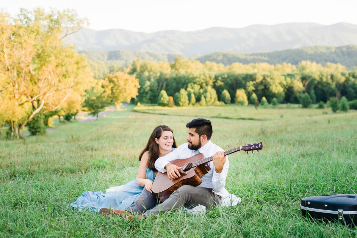 two people outside sitting on a blanket. girl listening as the guy plays the guitar.