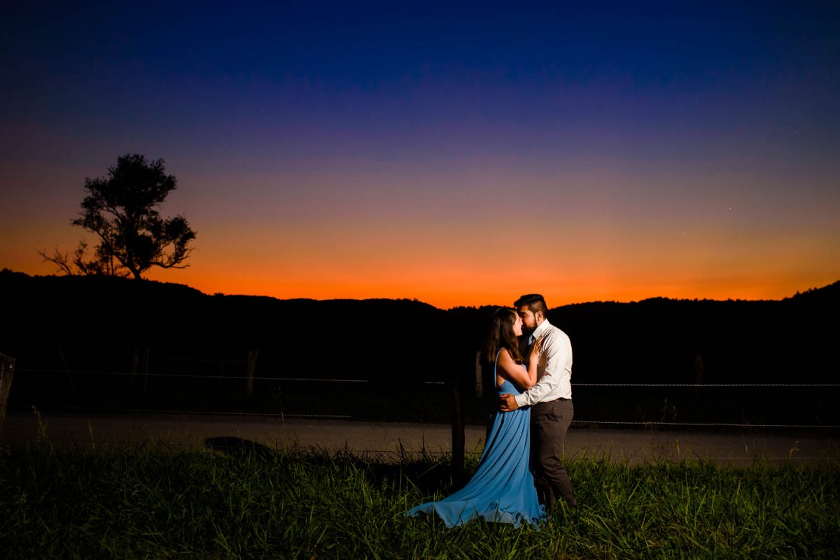 two people embracing at sunset in a field