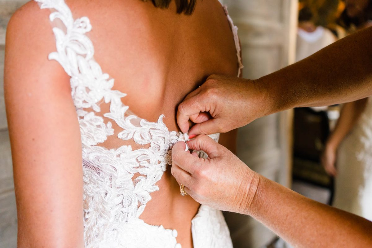 hands buttoning up lace wedding dress