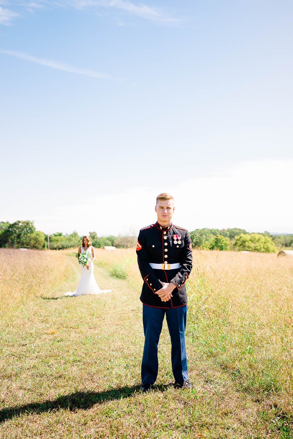 guy in marines uniform with bride to be in the background