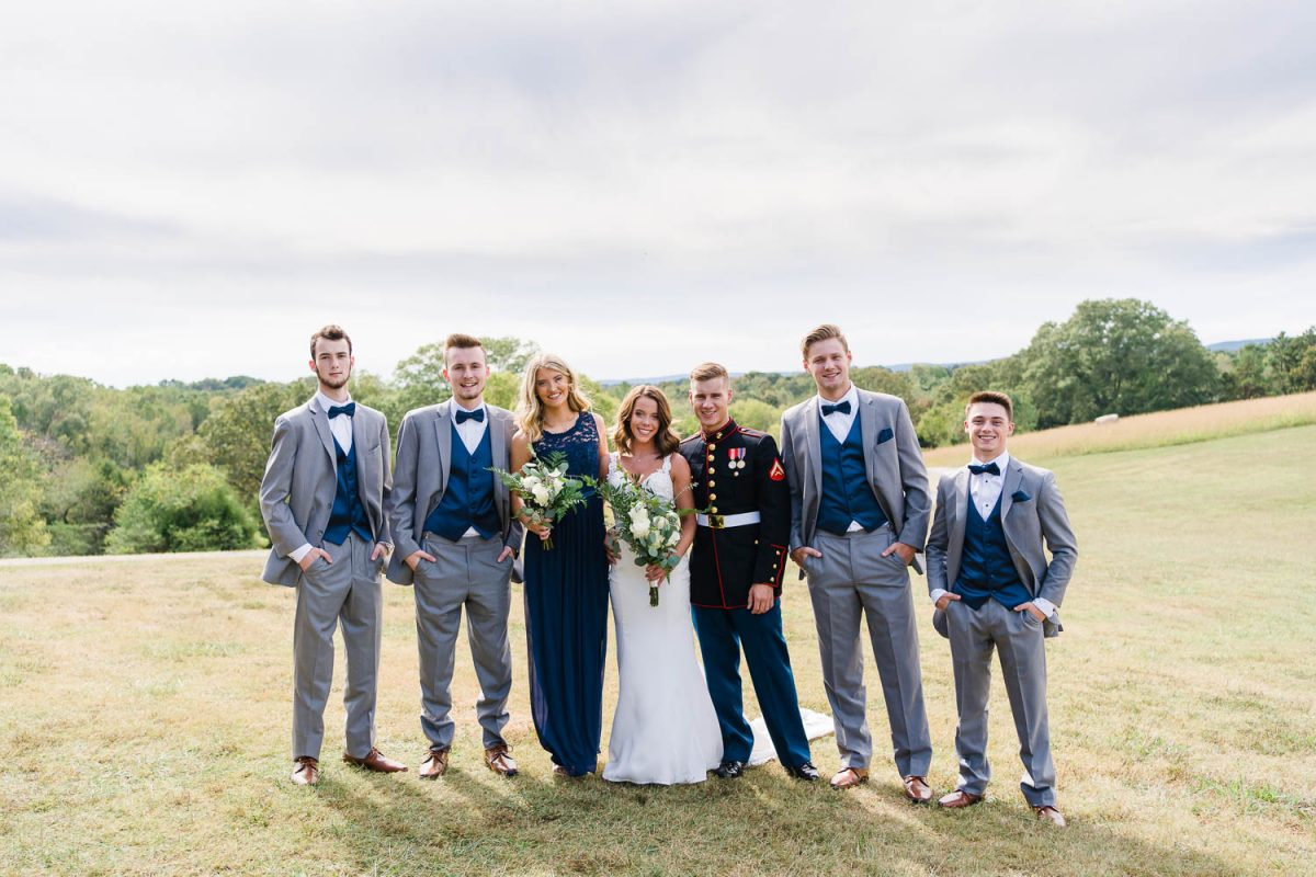 wedding party in gray and navy blue outside in a field