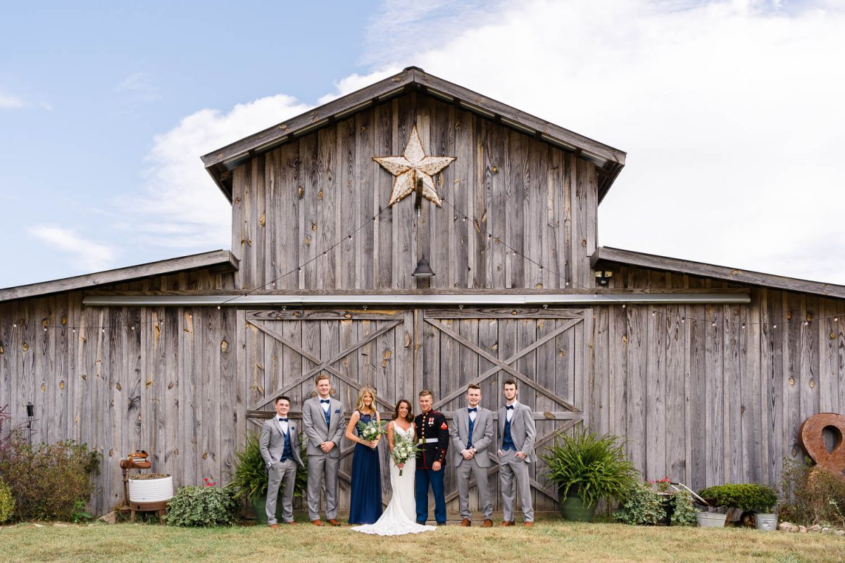 wedding party standing outside in front of a barn