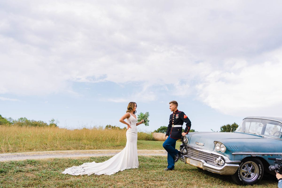 two people outside on marine uniform and wedding dress next to an antique blue car
