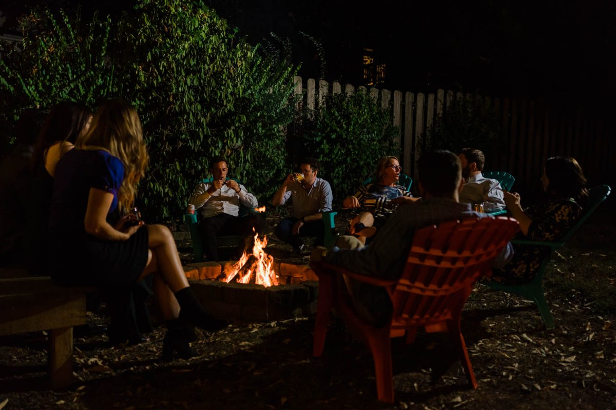 people outside sitting around a fire