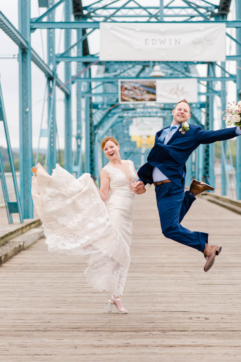 two people jumping wearing wedding clothes on the bluewalnut street bridge