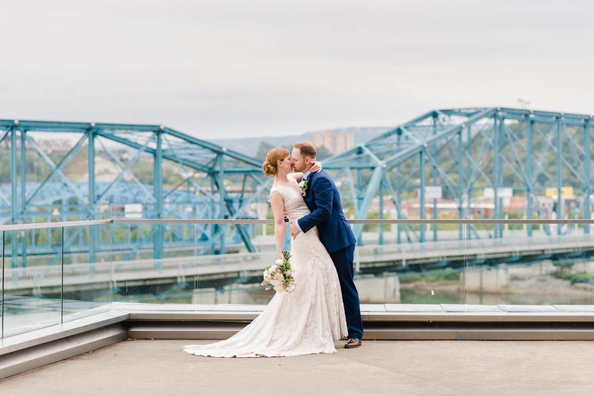 wedding couple withblue walnut street bridge in the background