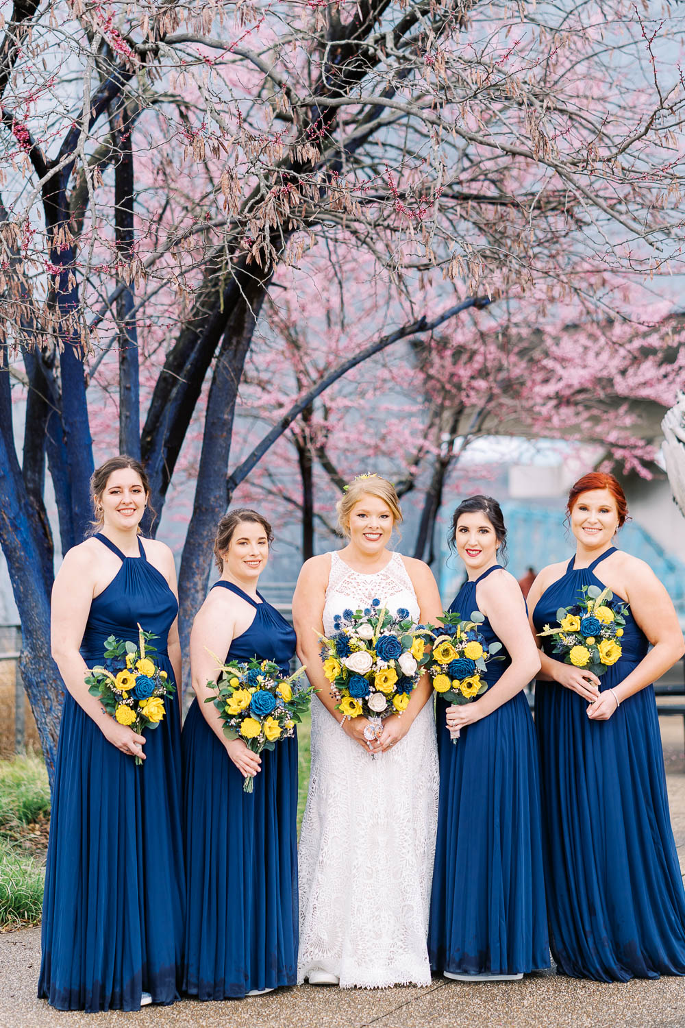 bride and bridesmaids in front of cherry blossoms