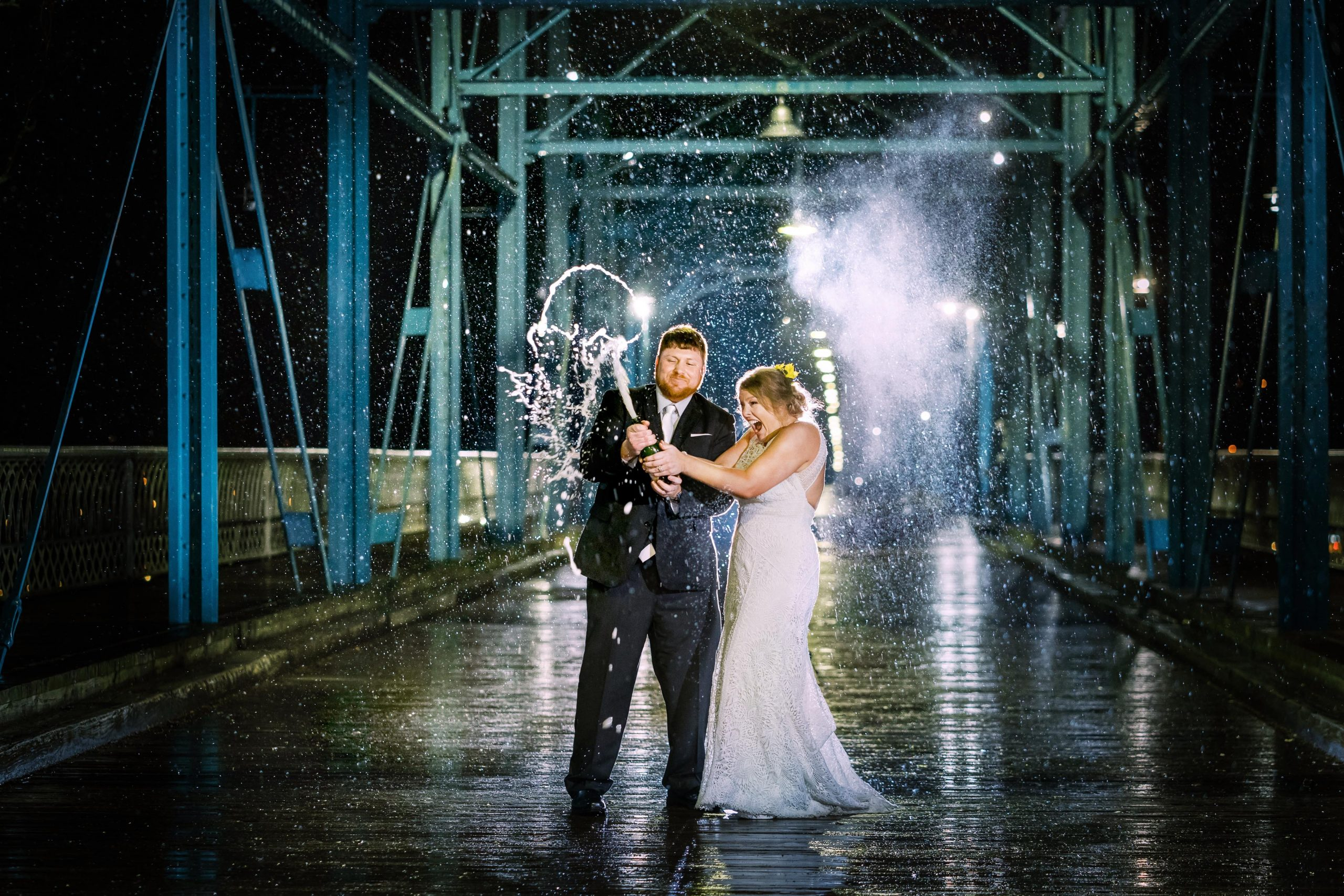 wedding couple popping champagne at night in the rain on the walnut street bridge in chattanooga