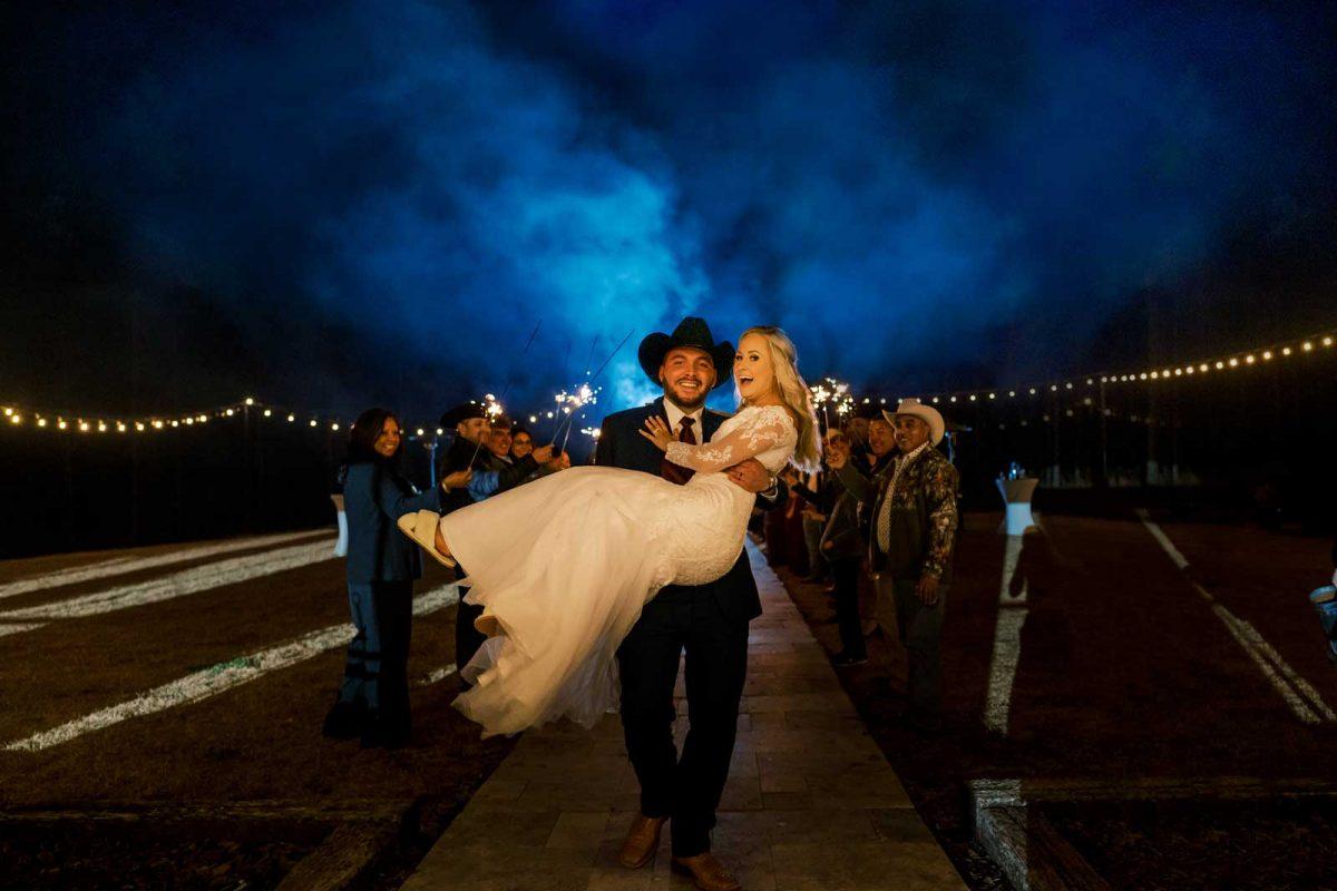 groom carrying his bride through blue smoke